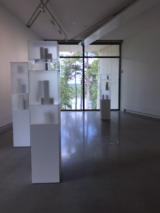 Edmund de Waal's ceramic vessels enclosed in glass cabinets stand parallel to the trees.